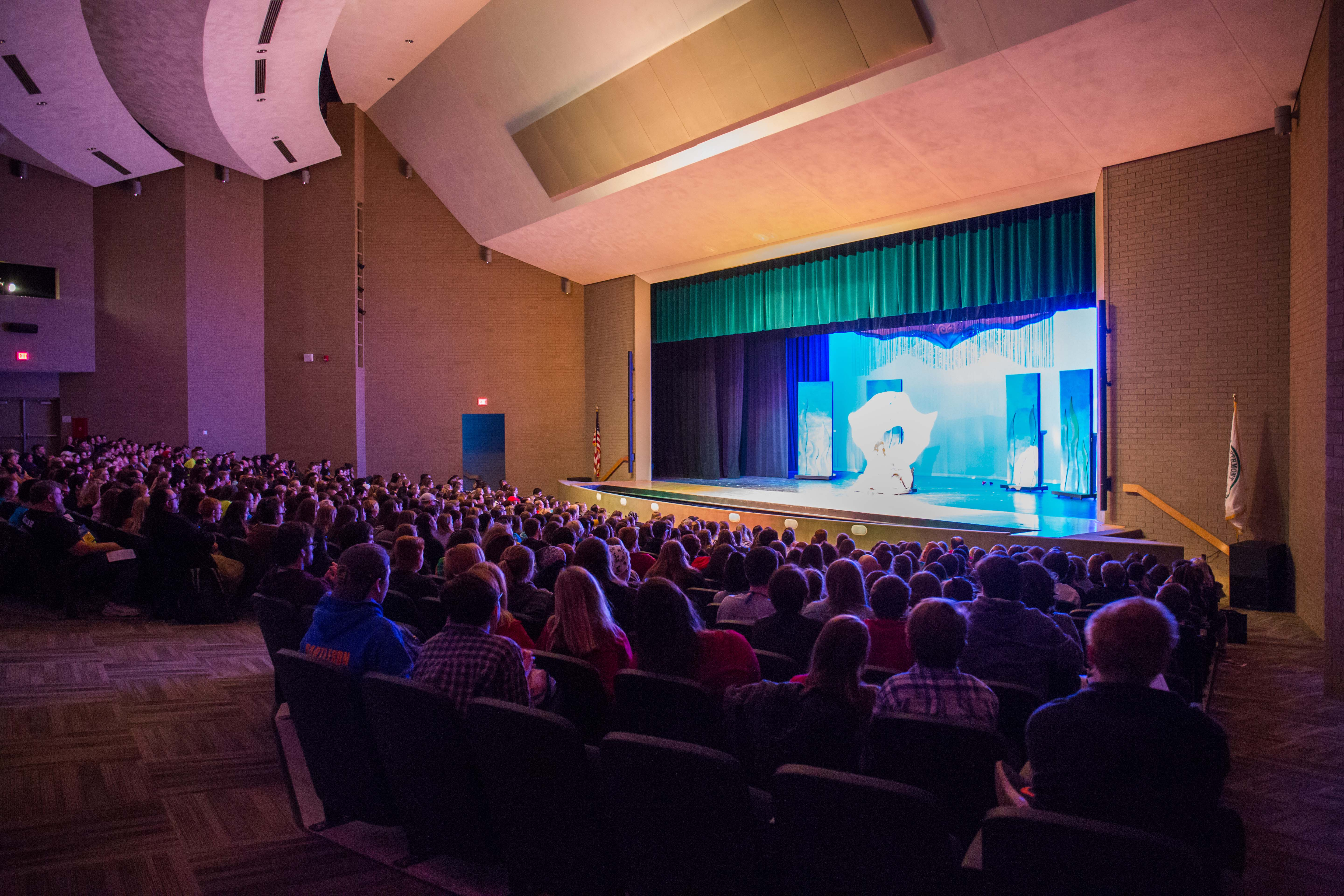 auditorium full of students watching a performance on stage