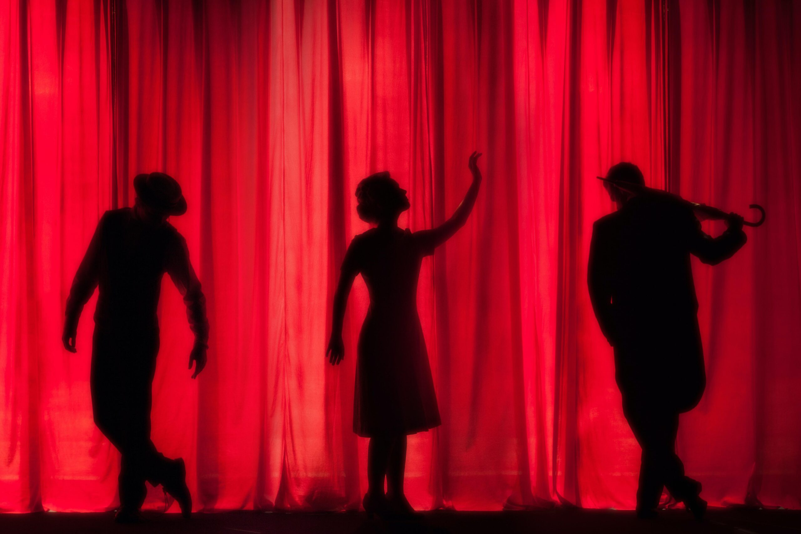 three figures in silhouette against a red curtain